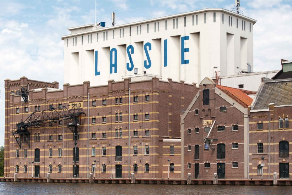 Foto van de oude en nieuwe delen van de Lassie fabriek aan de zaan. F.L.Snijders