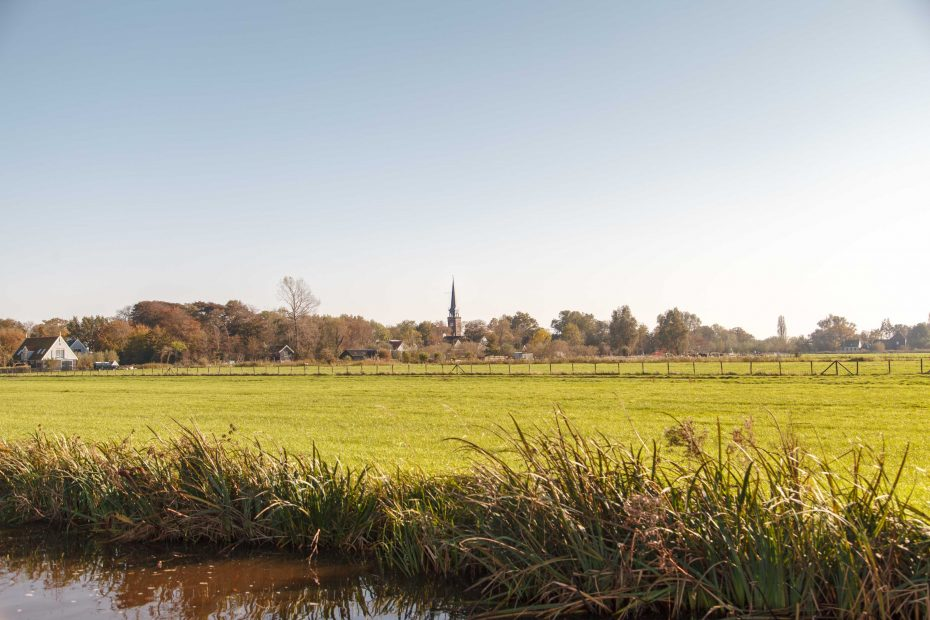 Foto met de kerktoren van Broek in Waterland in de verte. F.L.Snijders
