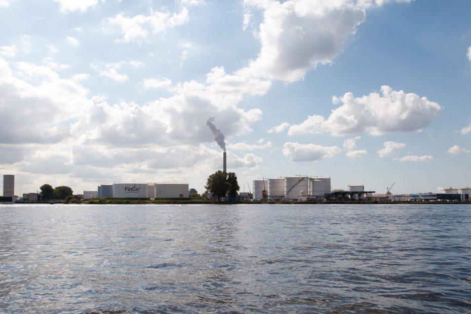 Foto van Petroleumhaven, Amsterdam vanaf het Noordzeekanaal, met schoorsteen Hemwegcentrale, F.L.Snijders