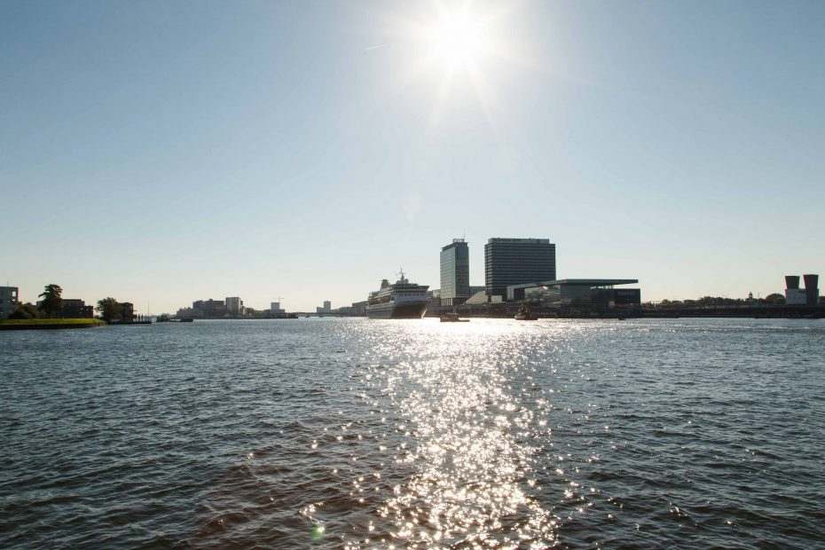 Foto met tegenlicht van het IJ richting Passengerterminal met cruiseschip, door F.L.Snijders